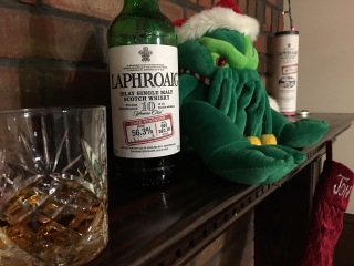 Laphroaig cask-strength whisky, in a glass before its bottle, sharing a mantle with Christmas Cthulhu.