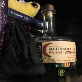 A whisky bottle containing dice sits on a bookshelf. Leaning against it is a filled black dice bag. Foreground: A d6 bearing the 2016 World Dice Day logo. Background: Books in The Vampire Files series, stacked horizontally, topped with a bookworm from the Giant Microbes plush figures collection.