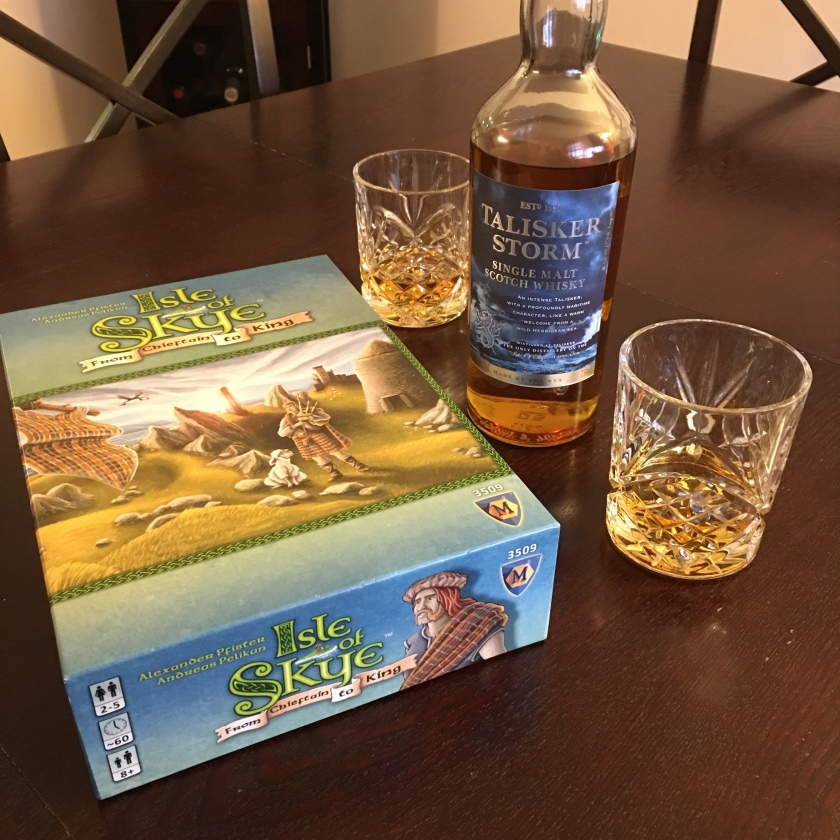 A bottle of Talisker Storm whisky sits between a pair of filled glasses, next to a boxed board game, Isle of Skye.