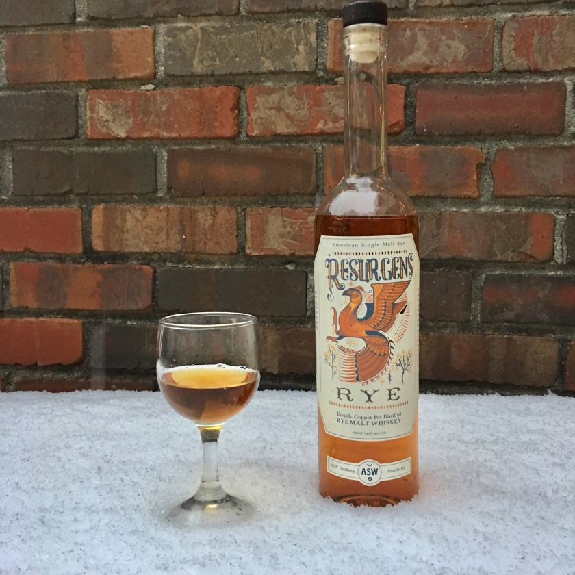 A bottle of Resurgens Rye and a glass of same sit on a snow-covered table in front of a brick wall.