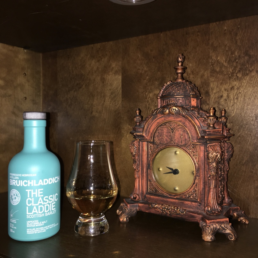 A small bottle of Bruichladdich Laddie whisky sits next to a filled Glencairn glass and tabletop clock.