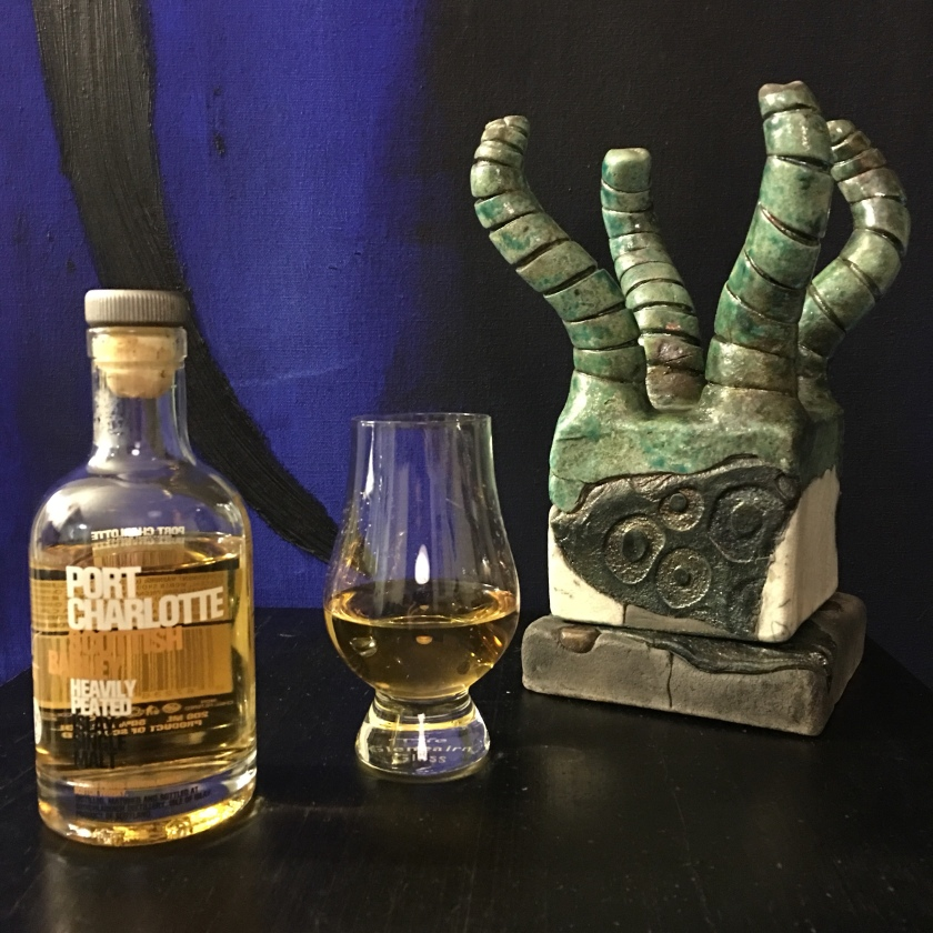 A bottle of Bruichladdich Port Charlotte whisky and a filled Glencairn glass sit alongside a small tentacled box, on a table in front of a painting in which a long black line dangles over a dark blue background.