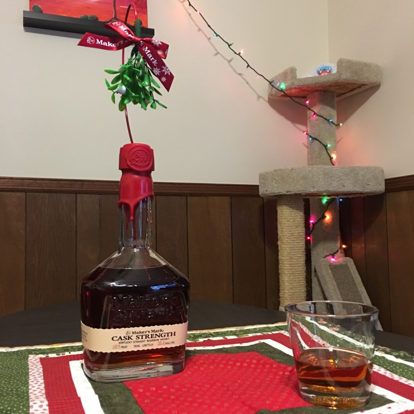 A bottle of cask-strength Maker's Mark bourbon, adorned with mistletoe, sit alongside a filled glass. In the background, a cat tree bears Christmas lights.