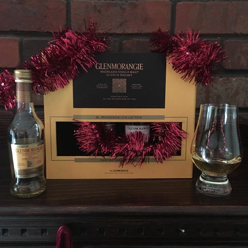 An opened 100-ml bottle of Glenmorangie Original (10YO) stands in front of a Glenmorangie tasting set gift box, the contents of which are obscured. Nearby, a Glencairn glass stands filled with whisky.