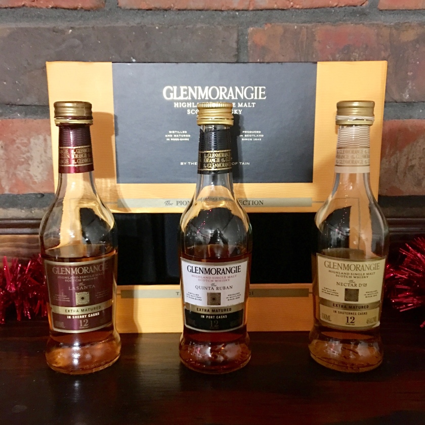 Three 100-ML bottles of Glenmorangie whisky, each about half-consumed, stand in front of the empty gift box in which they were packaged. They are three different 12-year-old varieties: The Lasanta, The Quinta Ruban, and The Nectar d'Or.