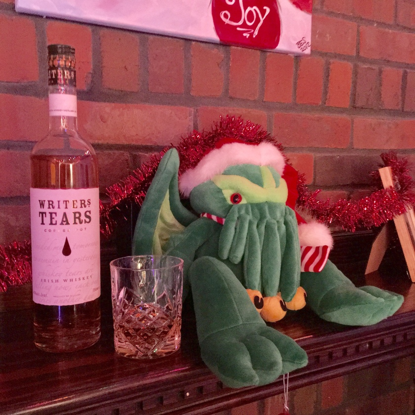 A bottle of Writer's Tears whisky sits next to a filled glass and Christmas Cthulhu.