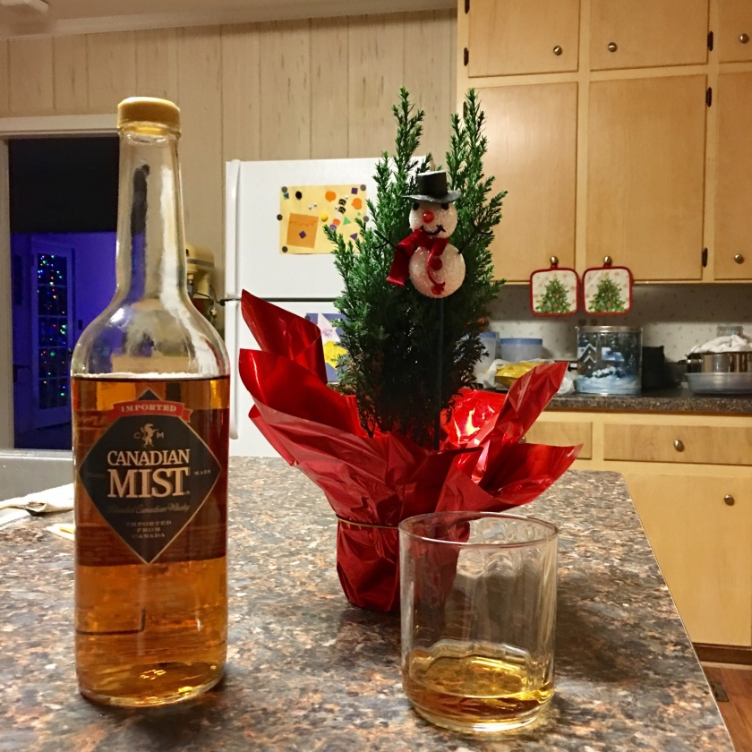 A bottle of Canadian Mist whisky sits next to a filled glass, next to a tiny tabletop Christmas tree. All of these items sit upon a kitchen counter.