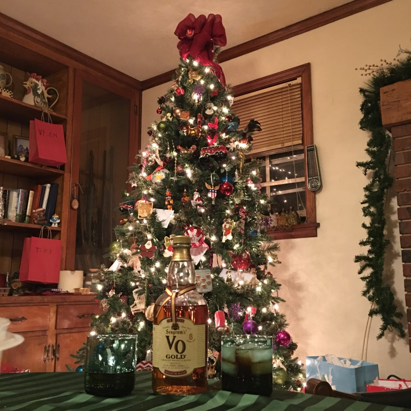 A bottle of Seagram's VO Gold sits next to a pair of glasses, in front of a Christmas tree.
