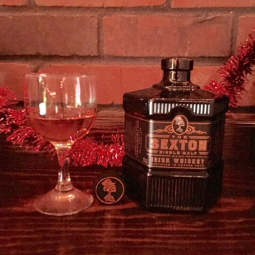 A bottle of The Sexton single malt Irish whisky sits next to a glass filled with same, on a mantel with red holiday garland.
