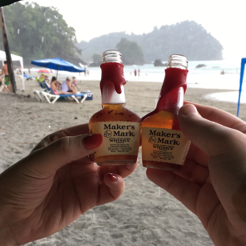 A pair of hands hold mini-bottles of Maker's Mark bourbon. In the background, rain begins to fall on a tropical beach.