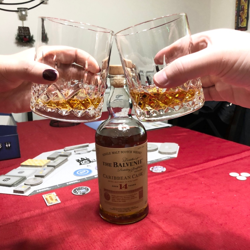 Two glasses full of whiskey clink in front of a bottle of Balvenie 14-year-old Caribbean cask-finished whisky.